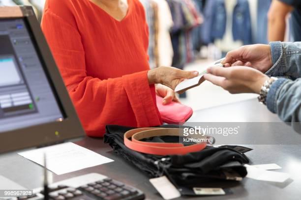 Senior Japanese woman signing on receipt