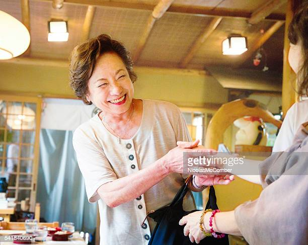 Senior Japanese woman smiles as she is greeted by friend
