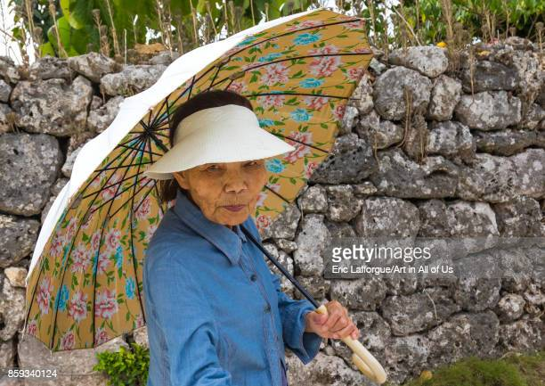 Senior japanese woman with an umbrella Yaeyama Islands Taketomi island Japan on September 1 2017 in Taketomi Island Japan