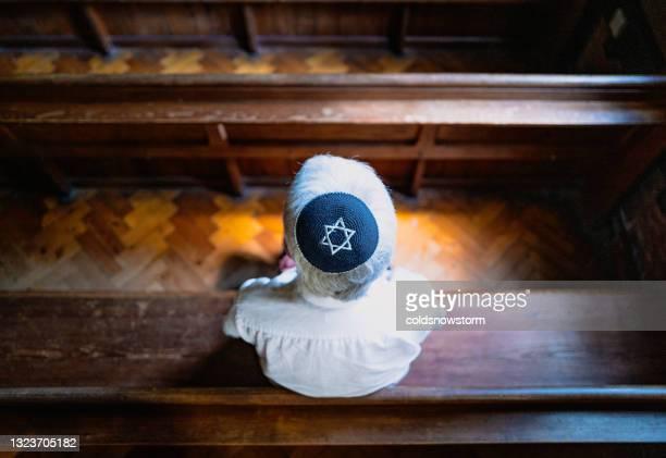 シナゴーグの中で祈る頭蓋骨の帽子をかぶった上級ユダヤ人男性 - ラビ ストックフォトと画像