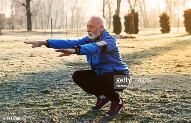 senior jogger doing stretching - squatting position stock pictures, royalty-free photos & images