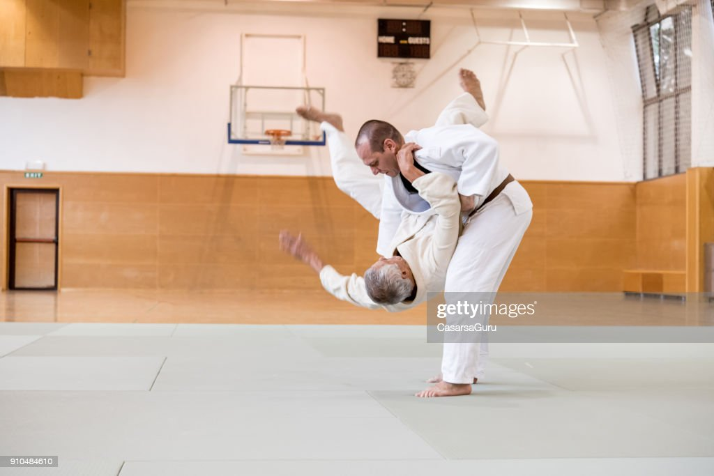 Senior Judo Fighter Mid Air, Forced to the Ground By His Opponent : Stock Photo