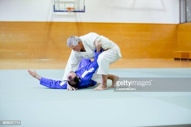 lutador de judô sênior, realizando um takedown - combat sport - fotografias e filmes do acervo