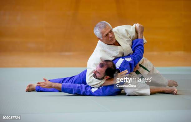 senior judoist holding his adversary to the ground - judo stock photos and pictures