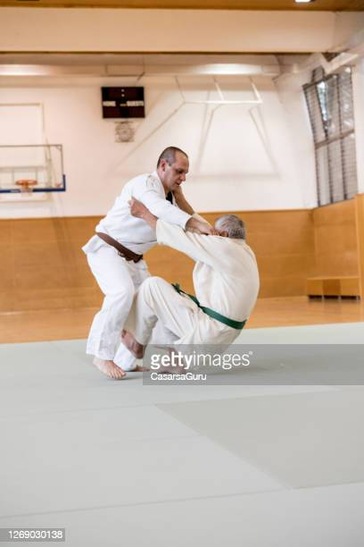 senior judoist using judo technique to throw his adversary over him - martial arts stock pictures, royalty-free photos & images