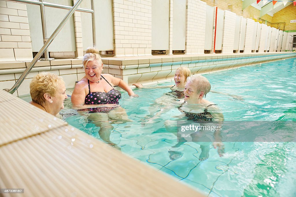 senior ladies gossip in pool : Stock Photo
