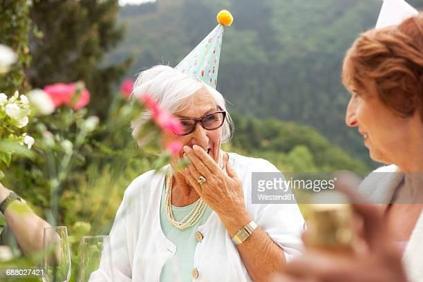 Senior ladies laughing at celebration, wearing party hats