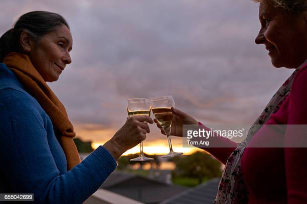Senior ladies share drinks at sunset