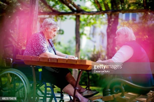 Senior Ladies Sitting on Backyard of Retirement Community