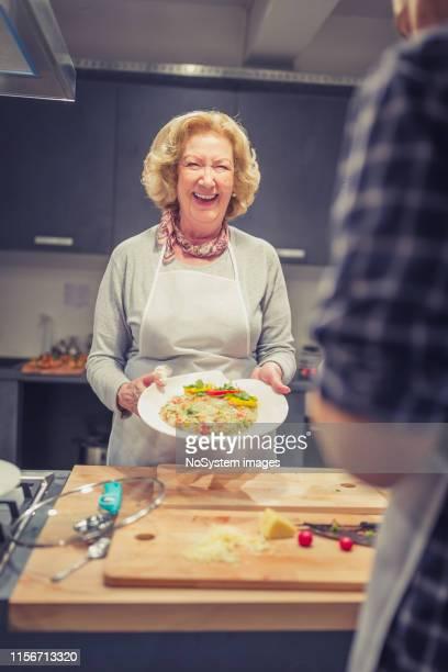 senior lady, un partecipante al corso di cucina con risotto - cultura italiana foto e immagini stock