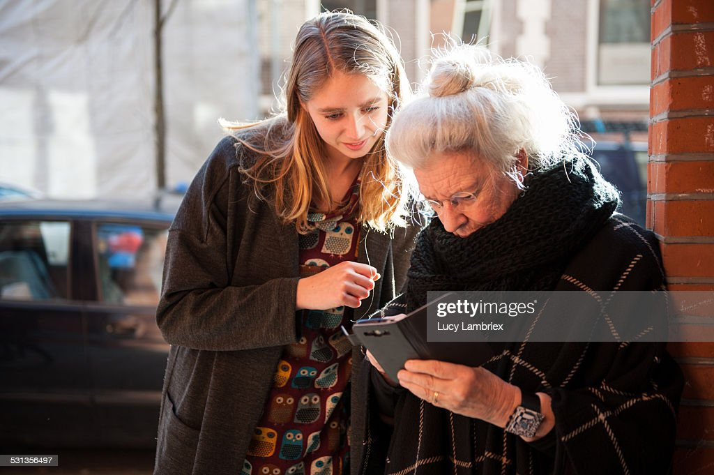 Senior lady and grandchild looking at smartphone : Stockfoto
