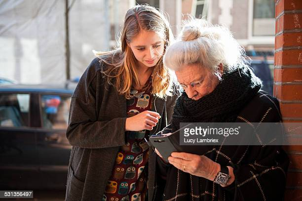 Senior lady and grandchild looking at smartphone