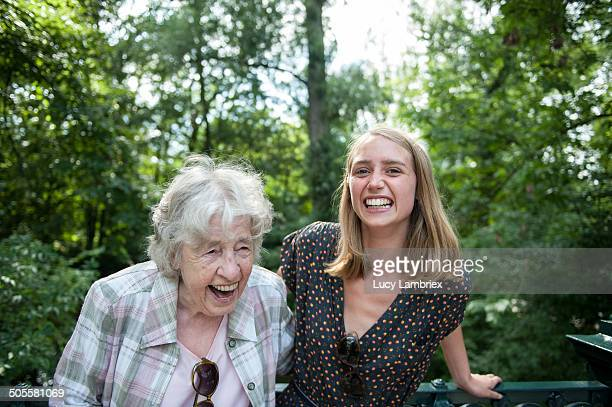 Senior (98) lady and young woman laughing in park