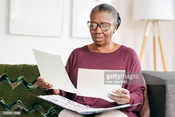 señora mayor en casa trabajando con documentos - documento legal fotografías e imágenes de stock