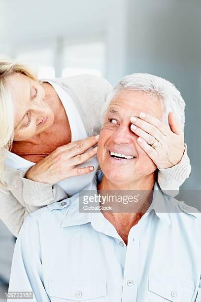 Senior lady covering eyes of her husband