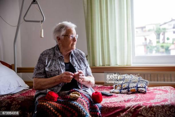 Senior Lady Häkeln in ihrem Zimmer im Ruhestand Gemeinschaft