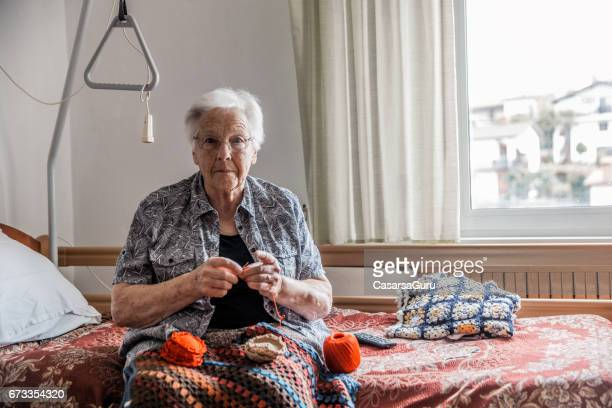 高齢女性の彼女の部屋でかぎ針編み引退コミュニティ - かぎ針編み ストックフォトと画像