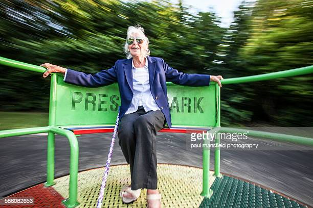 senior lady enjoying playground ride - young at heart stock pictures, royalty-free photos & images