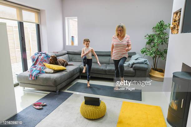 senior lady exercising indoors with her granddaughter - wellbeing stock pictures, royalty-free photos & images