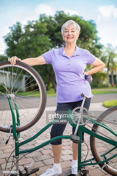 Senior lady fixing bike