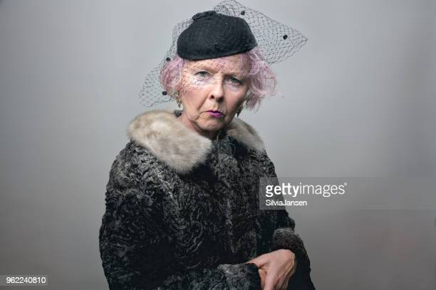 senior lady in retro style grief - fur coat stock pictures, royalty-free photos & images