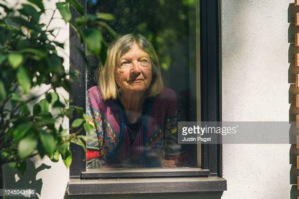 senior lady looking through window - anxiety stock pictures, royalty-free photos & images