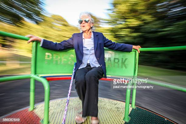 Senior lady on roundabout at playground