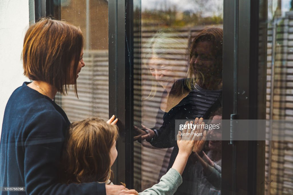 Senior lady speaking to daughter and granddaughter through window : Stock Photo