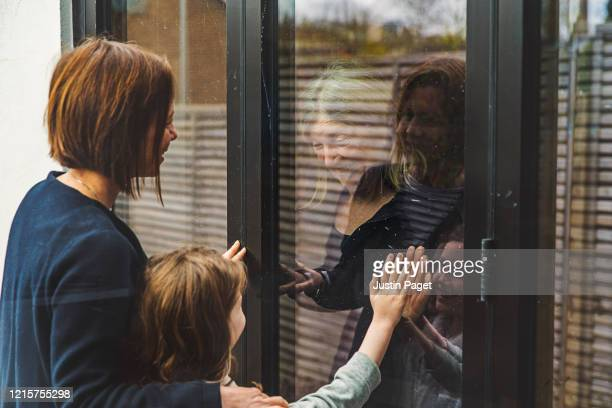 senior lady speaking to daughter and granddaughter through window - social distancing stock pictures, royalty-free photos & images