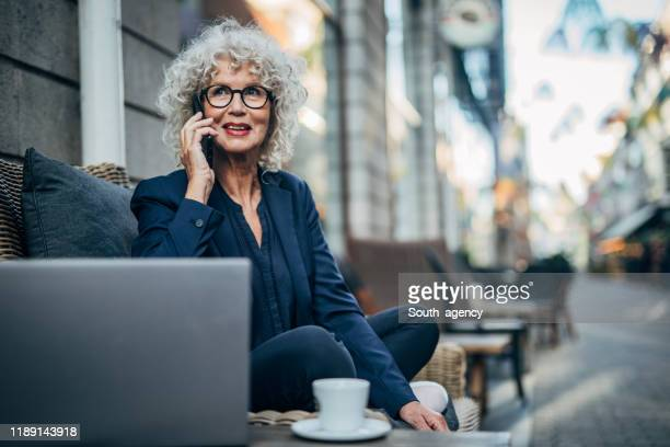 senior lady talking on mobile outdoors in cafe - businesswoman stock pictures, royalty-free photos & images