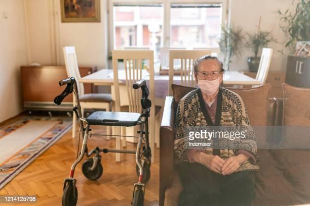 dame aînée avec un rouleauur marchant dans la maison pendant la quarantaine de maison de coronavirus - personnes avec déficiences photos et images de collection