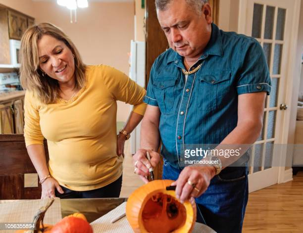 Senior Latin American couple carving pumpkins for Halloween