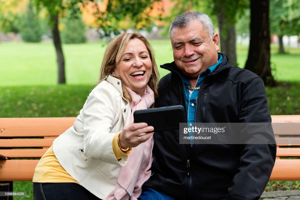 Senior Latin American couple taking a selfie outdoors. : Stock Photo