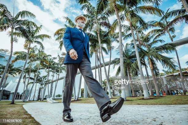 senior latino businessman walking back home after work in usa - wide angle stock pictures, royalty-free photos & images