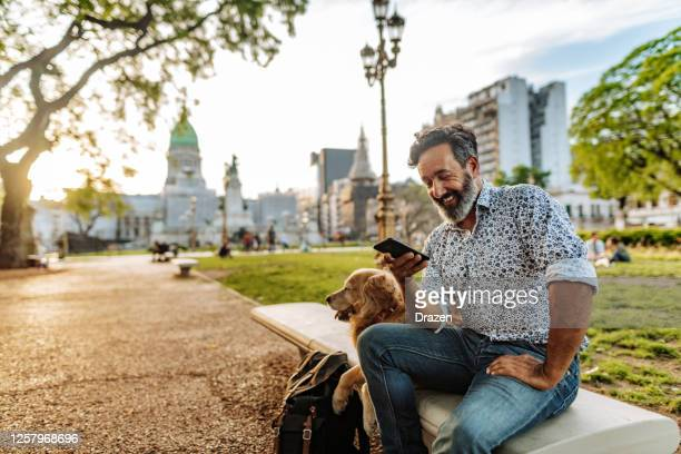 uomo latino anziano che cammina con il suo cane retriever anziano - argentina america del sud foto e immagini stock