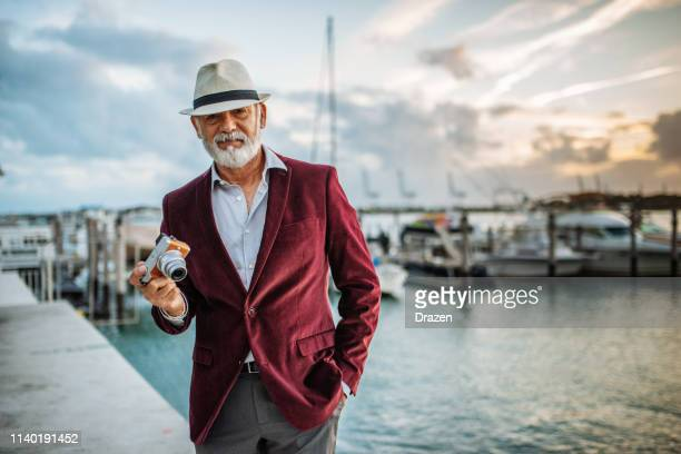 senior latino tourist traveling to sea side and using camera - bay of water stock pictures, royalty-free photos & images