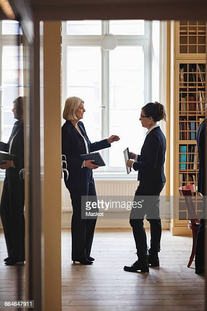 Senior lawyer discussing with female coworker while standing in library seen from doorway