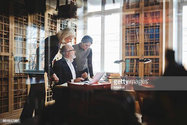 Senior lawyer discussing with female coworkers at table seen through glass in library