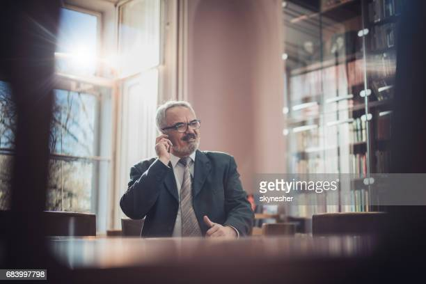 Senior lawyer having a conversation over mobile phone in the office.