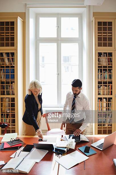 senior lawyer with male coworker researching in library - law office stock photos and pictures