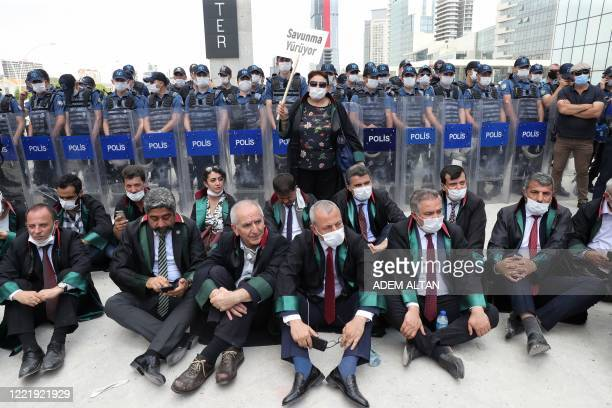Senior lawyers protesting against a draft bill governing the organisation of bar associations sit on the ground during a rally in front of Turkish...