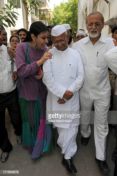 Senior leader of the India Against Corruption Movement Anna Hazare is briefed by activist and dancer Mallika Sarabhai as he arrives at the Gujarat...