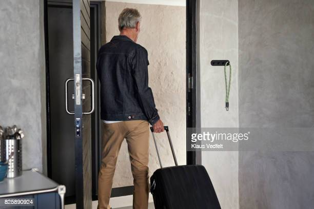Senior leaving apartment with rolling suitcase