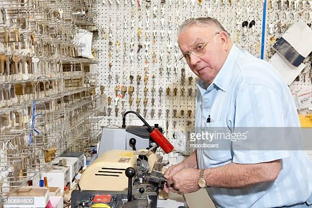Senior locksmith looking away while making key in store