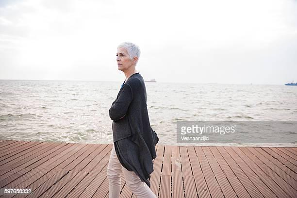 Senior lonely woman walking near coast