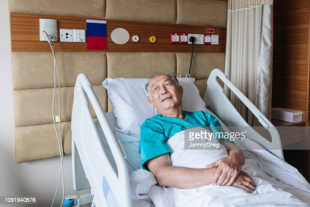 senior malaysian man lying in hospital bed and looking away - patience stock pictures, royalty-free photos & images