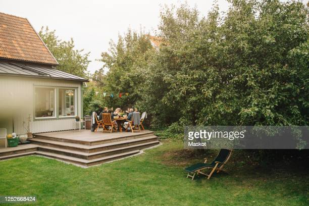 senior male and female friends enjoying dinner while sitting dining table during garden party - active seniors stock pictures, royalty-free photos & images