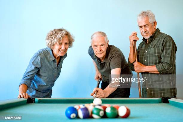 senior male and female friends playing pool ball - old men playing pool stock pictures, royalty-free photos & images