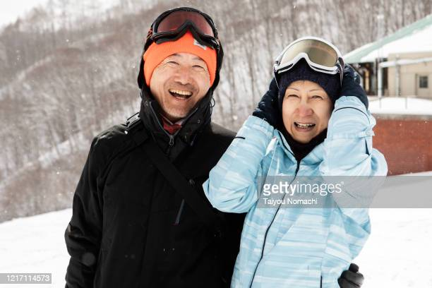 senior male and female portraits taken on the ski slopes - disruptagingcollection stock pictures, royalty-free photos & images