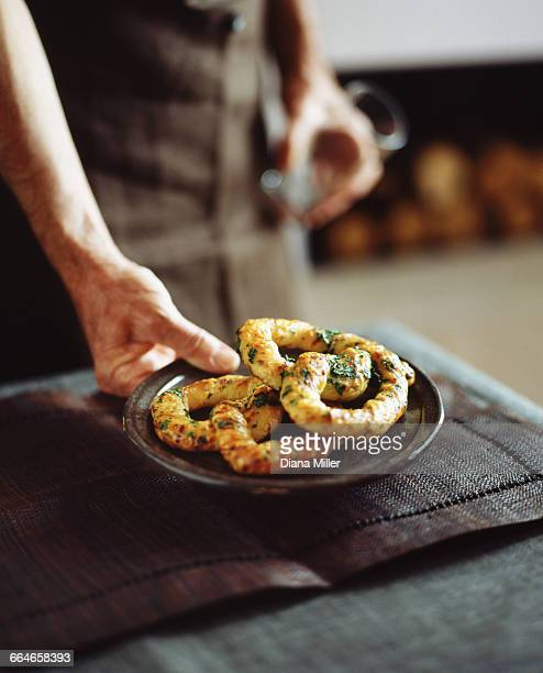 Senior male baker placing savoury pretzels on table